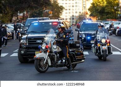 Hoboken, NJ / USA - 31 10 2018: police officer on motorcycle patrol street