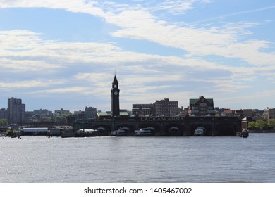 Hoboken, NJ/USA: May 11, 2019 – Lakawanna Ferry Terminal in Hoboken New Jersey and its historic Clock Tower skyline as seen in the distance from the Hudson River in late afternoon.
