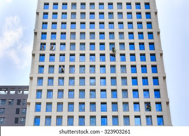 Hochiminh City, Vietnam - September 19, 2015: Dangerous job of the workers cleaning the glass surface m of a new building completed