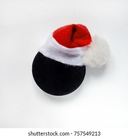 Hockey black washer in santa hat close-up on white background isolated flat lay