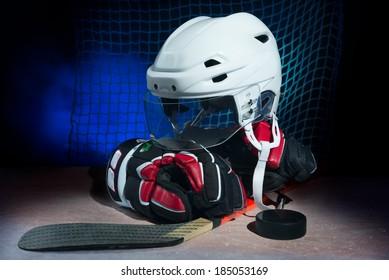 Hockey gloves,helmet and stick lay on ice.