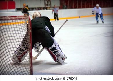 Hockey goalie in generic black equipment protects gate