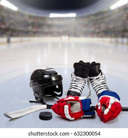 Hockey helmet, gloves, skates, stick and puck on ice in fictitious arena with fans in the stands and copy space. 3D rendering of hockey rink arena.