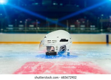 Hockey helmet and puck laying on face off spot