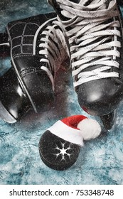 Hockey men's skates and washer with a cap of Santa close-up , concept of Christmas winter tournaments on a blue background