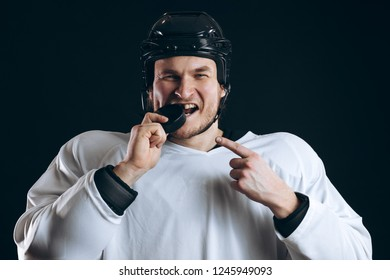 Hockey player bitting the puck with broken tooth and pointing at it with finger. Ice-hockey, extreme sports and Hobby Concept.