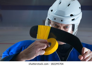 Hockey player in blue jersey taping his stick. Close view