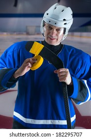 Hockey player in blue jersey taping his stick.