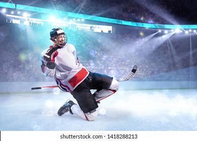 Hockey player celebrate goal. He very happy around ice rink arena