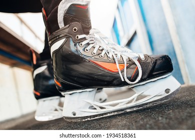 Hockey player feet in skates on the bench overboard are eagerly preparing to enter the game - player debut