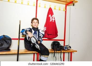 Hockey player putting on ice skates in locker room