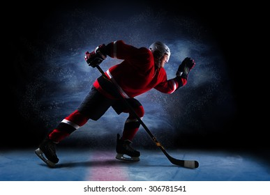 Hockey player in red uniform run across ice rink. Over dark background