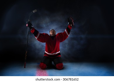 Hockey player sitting on his knees with raised arms