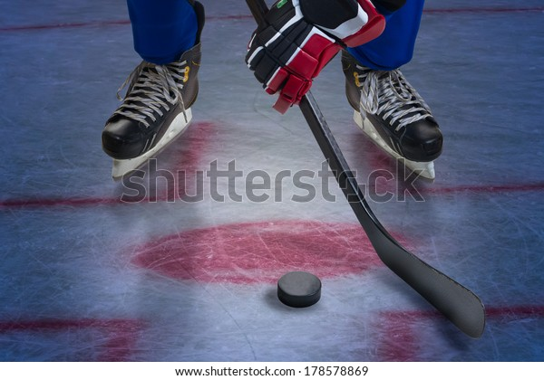 Hockey player stand on face-off spot. Legs only view