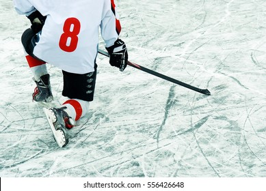 Hockey player with stick on the ice.