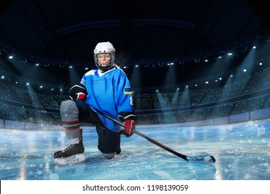 Hockey player with stick standing on one knee