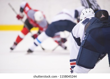The hockey player is waiting for the puck to play.
