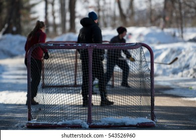 Hockey players playing street hockey in winter