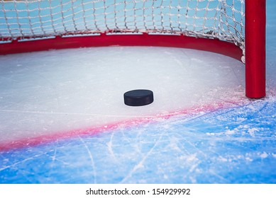 Hockey puck crossing red goal line. Close view