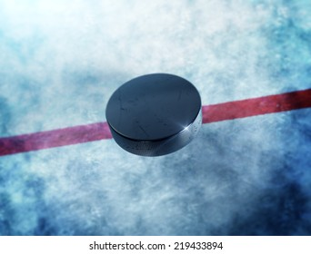 Hockey puck in the middle above the ice and red line with lens flare around puck.