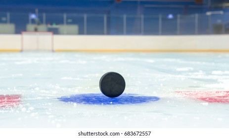 Hockey puck on blue face off spot. In front of hockey goal