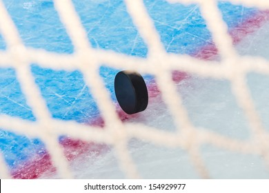 Hockey puck stand on side on goal line. View through goal net