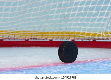 Hockey puck stand on side in front of goal net. Close view