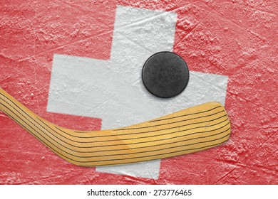 Hockey puck, hockey stick and the image of the Swiss flag on the ice
