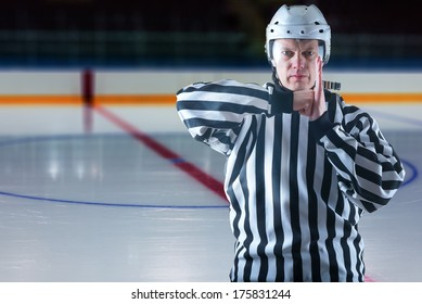 Hockey referee demonstrate boarding penalty. Ice rink on background