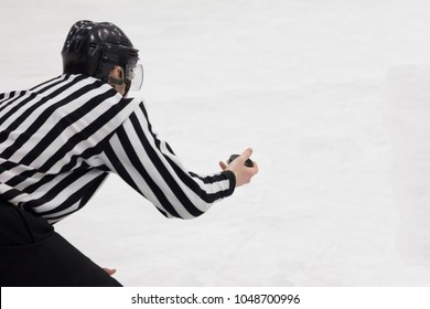 Hockey referee holding a puck in face off position. Hockey judge. Back view. White background, isolated.