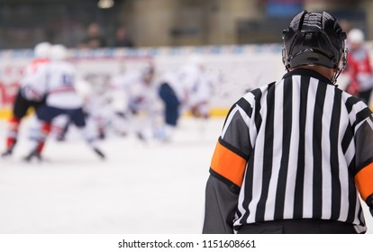 Hockey referee on the ice watching the game.