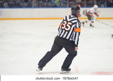 Hockey referee rides on ice on ice skates, hockey players
