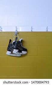 Hockey skate hanging in locker room over yellow background with copy space in portrait
