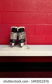 Hockey skate over white bench in locker room with red background and copy space in portrait position. Close view