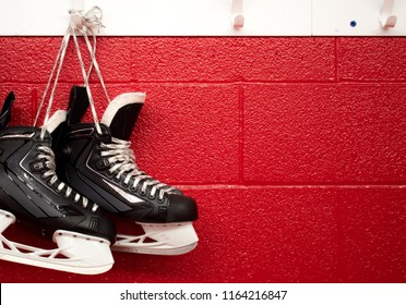 Hockey skates hanging in locker room with copy space in red background