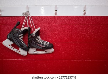 Hockey skates hanging in locker room over red background with copy space