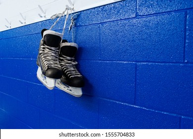 Hockey skates hanging in locker room over blue background with copy space