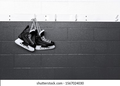 Hockey skates hanging in locker room in black and white background with copy space