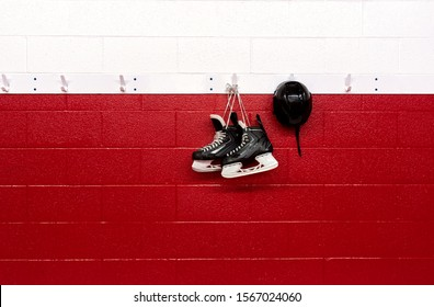 Hockey skates hanging in locker room with helmet over red background with copy space