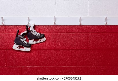 Hockey skates hanging over red wall in locker room with copy space