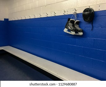 Hockey skates and helmet hanging in locker room with blue background and copy