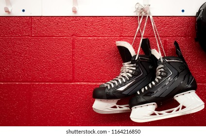 Hockey skates and helmet hanging in locker room with copy space in red background