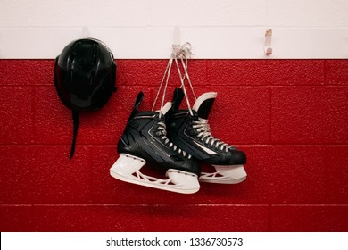 Hockey skates and helmet hanging in locker room with red background and copy space