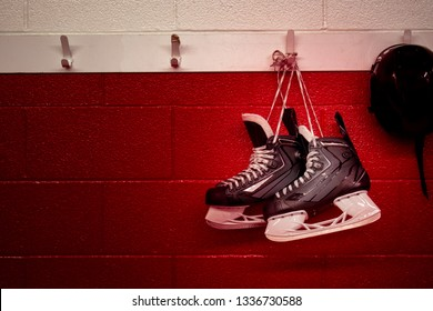 Hockey skates and helmet hanging in locker room with red gradient background and copy space