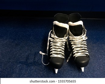 Hockey skates in locker room floor over blue background with copy space. Top view