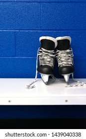 Hockey skates on white bench in locker room with copy space in portrait position