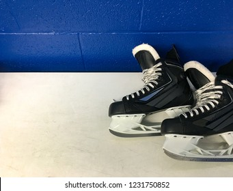 Hockey skates over white bench in locker room with copy space