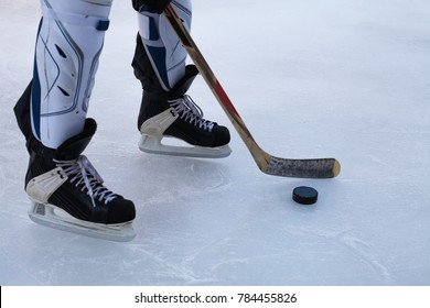 Hockey skates, senior shin guards, stick and puck on ice