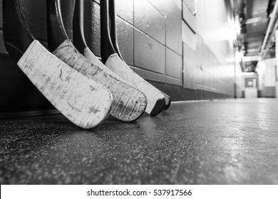Hockey stick blades laid on a dirty arena floor - Shallow depth of field - Black and white