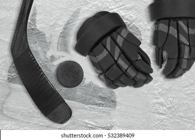 Hockey stick, gloves and puck on the ice arena. Concept